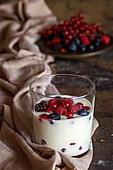 Yoghurt with berries in a glass on a wooden table