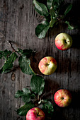 Four apples with leaves on a wooden board