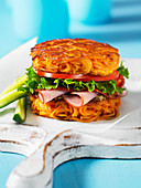 A ham, salad and tomato sandwich made with a spiralized sweet potato bun