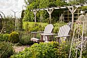 Sitzplatz mit Holzstühlen vor Pergola im Garten
