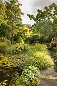 Gartenteich im Herbst, eingefasst mit Stauden und Gräsern (Les Jardin de Castillon, Frankreich)