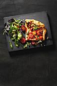 A slice of cheesy tomato tart with salad