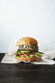 A chicken burger with avocado, sesame seeds and yoghurt sauce