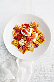 Ravioli with tomato sauce, yoghurt and mint