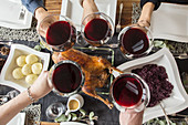 People raising their glasses of red wine over a roast goose with red cabbage and potato dumpling