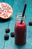 A blackberry and pomegranate smoothie in a bottle with a straw