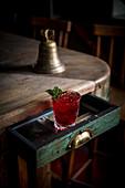 Roter Cocktail mit Eiswürfeln und Minzblättechen