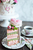 A slice of strawberry and pistachio cake decorated to look like a silver birch