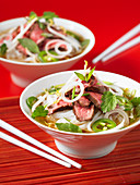Two bowls of Pho Bo (Vietnamese noodle soup) with beef