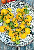 Frische gelbe Tomaten auf gemustertem Teller