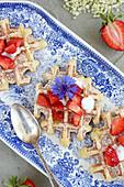 Erdbeer-Holunder-Waffeln auf blauem Teller mit Kornblume und Holunderblüten