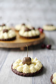 Chocolate tarts with vanilla cream and chocolate cherries