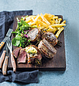 Fillet steaks wrapped in bacon, with rosemary and fries