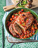 Roasted ground beef wrapped in bacon with tomatoes, olives and capers