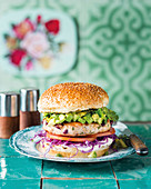 A chicken and bean burger with avocado salsa and red cabbage