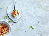 Pasta mit Tomaten und Basilikum in Schälchen und auf Gabel (Aufsicht)