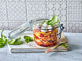 Spicy pasta salad with mozzarella to take away in a flip-top jar