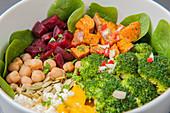 Buddha Bowl mit Babyspinat, Süsskartoffeln, Brokkoli, Mango, Feta, Kichererbsen und Roter Bete