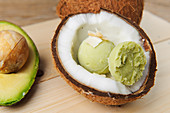 Avocado and coconut ice cream served in a coconut half
