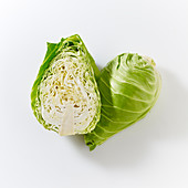 Pointed cabbages, whole and halved, on a white surface