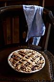 Pflaumen-Pekannuss-Pie auf altem Lederstuhl mit blauem Geschirrtuch