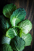 Several savoy cabbage leaves on a wooden background