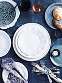 Gedeckter Tisch mit blau-weißem Geschirr, Besteck, Gläsern und Brot
