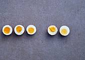 Five hard boiled egg halves on a grey background