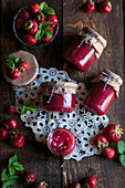 Strawberry jam in glass jars on a lace doily