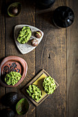 Guacamole in Avocadoschalen auf rustikalem Holztisch