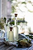 Geschenkflaschen mit Hollersirup auf Geschirrtuch