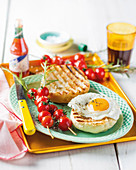 Tomato and rosemary skewers with a grilled bread roll and fried egg