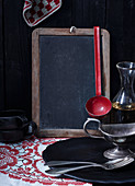 A blackboard and various vintage kitchen utensils