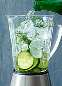 Ingredients for cucumber sangria with crushed ice in a blender