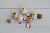 Painted Easter eggs and egg shells on white wooden surface