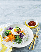 Rice with vegetables, fried egg and a spicy chilli sauce