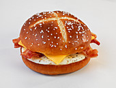 A lye bread roll with bacon, cheese and fried egg