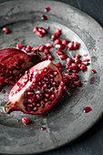 A pomegranate, sliced open, on a metal plate