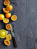 Orangen, teilweise ausgepresst mit Saftpresse auf Holzuntergrund