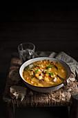 Kartoffelsuppe mit Lauch und Pancetta auf rustikalem Hocker