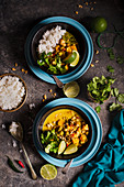 Vegeterian thai curry with squash and chickpeas, lime, coriander and toasted peanuts, view from above