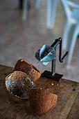 Alter Kokosnussschaber mit leeren Kokosschalen auf Holztisch