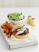 A mushroom burger with chips and salad