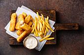 Fish and Chips mit Remoulade (Fastfood, England) auf dunklem Untergrund