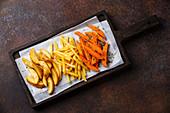 Kartoffelschnitze, Pommes Frites und Süsskartoffelspalten auf Ofenblech