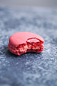 Half eaten pink macaron on grey background