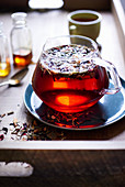 Loose leaf tea floating in red tea in a glass teapot with honey and mug