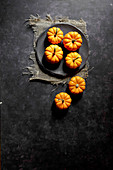 Small orange pumpkins on a black plate with a black background (top view)