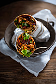 Vegan tortilla wraps filled with pulled jackfruit, dried tomatoes, red onions, cucumber and lettuce