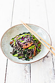 Black bean noodles with palm kale, mange tout and marinated beef